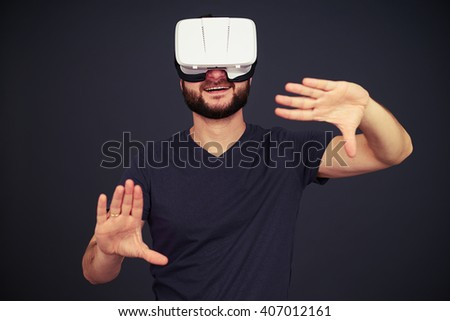 Beard man touch something with two arms in virtual reality, on black background - stock photo