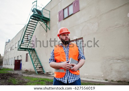 Beard worker man suit construction worker in safety orange helmet stay near big industrial stairs.