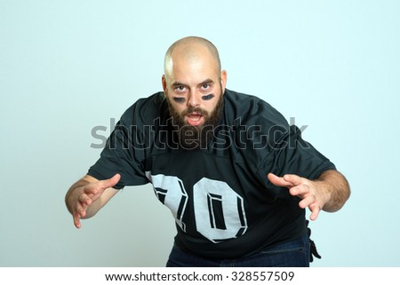 bearded american football player is looking in to the camera - stock photo