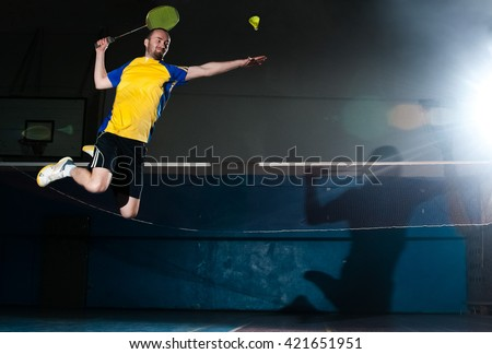 Bearded  badminton player in sport outfit jumping and making a racket swing on the fly. Artistic studio lighting and lens flare effect.