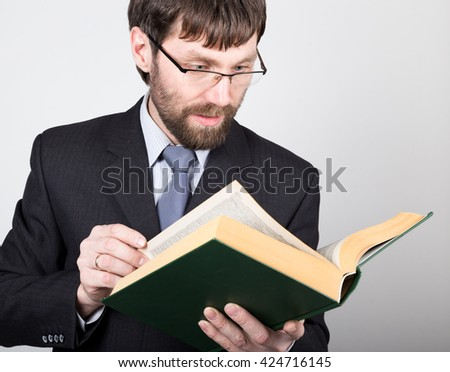 bearded businessman in a business suit and tie, reading a thick book - stock photo