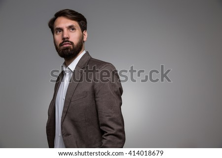 Bearded businessman in suit looking away from the camera on grey background. Mock up