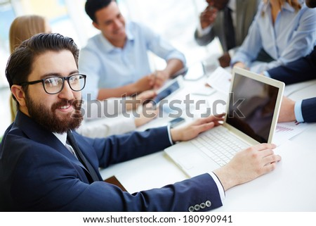 Bearded businessman looking at camera at meeting with group of partners interacting on background - stock photo