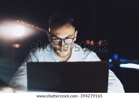 Bearded businessman wearing glasses working on modern loft office at night. Man using contemporary notebook texting document, blurred background. Horizontal, film effect, bokeh - stock photo