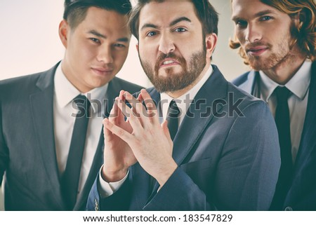 Bearded businessman with evil expression - stock photo
