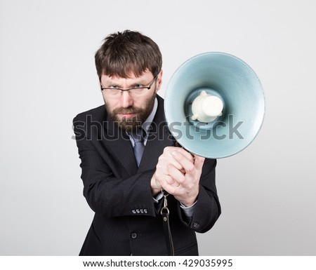 bearded businessman yelling through bullhorn. Public Relations. man expresses various emotions. photos of young businessman wearing a suit and tie
