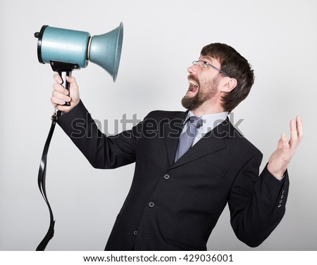bearded businessman yelling through bullhorn. Public Relations. man expresses various emotions. photos of young businessman wearing a suit and tie - stock photo