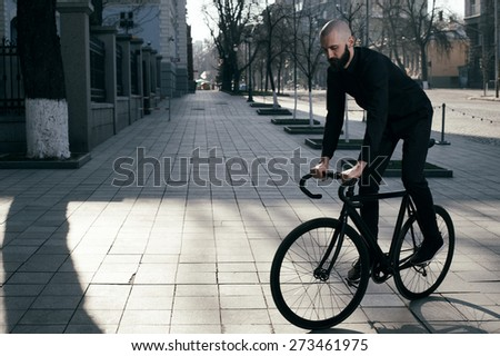 bearded caucasian bald man rides black fix bicycle near old restored building. He rides in  morning light in cobbled street. Street is empty. Man is wearing black shirt and trousers and sneakers.  - stock photo