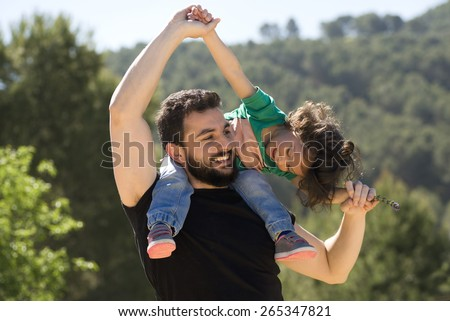 Bearded father and baby girl playing outdoors. Happy image of single father. - stock photo