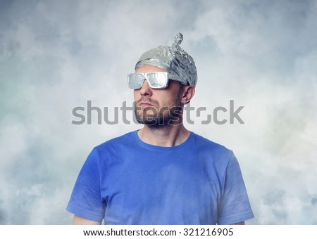 Bearded funny man in a cap of aluminum foil. Concept art phobias - stock photo