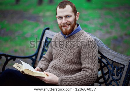 bearded guy reading a book in the park - stock photo
