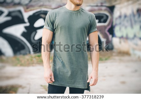 Bearded guy wearing green blank t-shirt and black jeans, standing on the street - stock photo