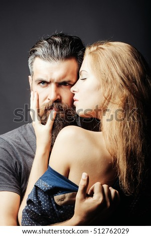 bearded handsome man and female slim flexible body of young pretty sexy woman or girl with bare back has long blonde hair embracing