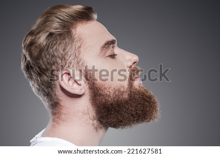 Bearded handsome. Side view of handsome young bearded man keeping eyes closed while standing against grey background - stock photo