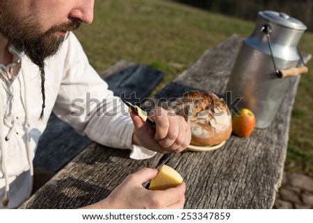 bearded hermit eating cheese and bread on a wooden table - stock photo