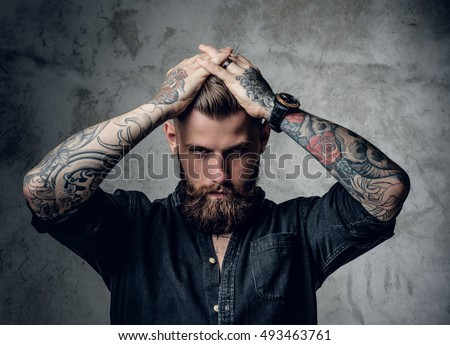 Bearded hipster male with tattoo on arms holding hands on his head.
