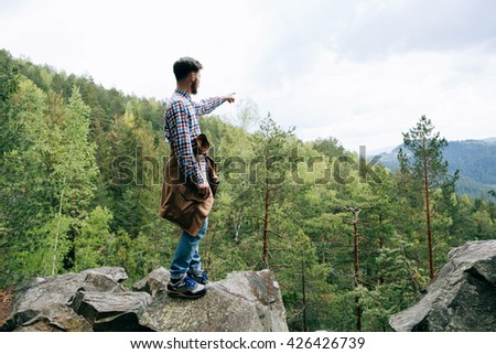 bearded hipster tourist man standing on a rock and hand pointing direction in mountains - stock photo