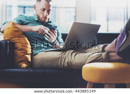 Bearded Hipster working Laptop modern Design Interior Studio Loft.Men Relaxing Vintage Sofa,Use Contemporary Notebook,Touching Smartphone.Blurred Background.Creative Business Startup Idea.Film,flare - stock photo