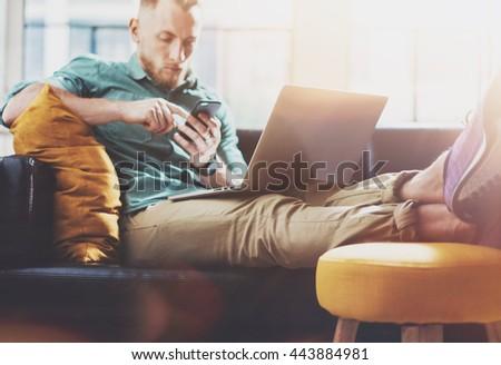 Bearded Hipster working Laptop modern Design Interior Studio Loft.Men work Vintage Sofa,Use Contemporary Notebook,Touching Smartphone.Blurred Background.Creative Business Startup Idea.Film flare - stock photo