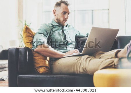 Bearded Hipster working Laptop modern Interior Design Loft Office.Man work Vintage Sofa,Use contemporary Notebook,typing keyboard.Blurred Background.Creative Business Startup Idea.Horizontal,Film - stock photo