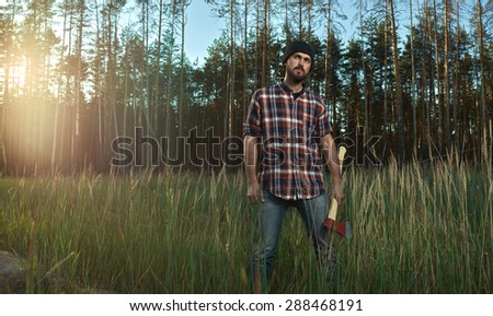 Bearded Lumberjack in Hat holding a big Ax in his Hand - stock photo