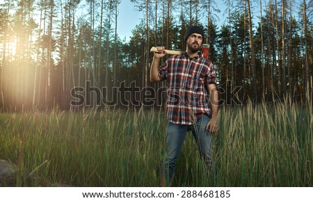 Bearded Lumberjack in Hat holding a big Axe on his Shoulder in Forest - stock photo
