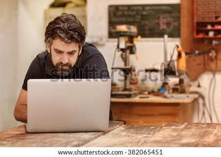 Bearded male designer working on his laptop on his workbench in his studio and workshop space, with woodwork machinery and tools behind him - stock photo