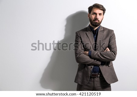 Bearded male in suit with crossed arms standing against white wall. Mock up
