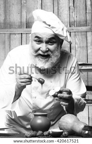 Bearded man cook in chef hat with apple nuts pumpkin and honey on wooden background, black and white