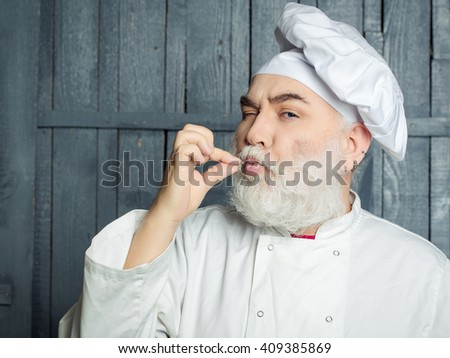 Bearded man cook in chef hat with fingers near mouth in studio on wooden background