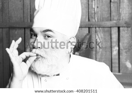 Bearded man cook in chef hat with fingers near mouth in studio on wooden background, black and white