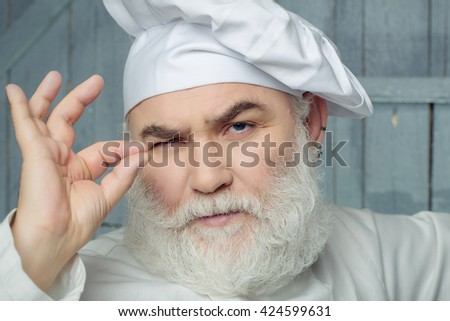 Bearded man cook with serious face in chef hat with ok gesture in studio on wooden background