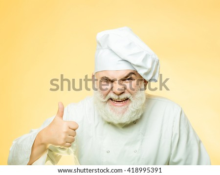 Bearded man cook with winking face in chef hat with thumb up in studio on yellow background