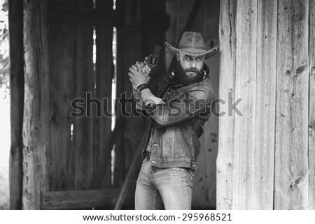 Bearded man. Cowboy. Shooting - stock photo