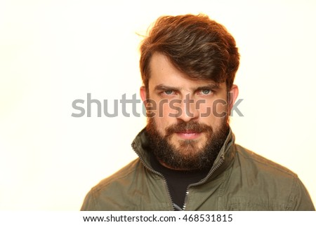Bearded man dressed in khaki jacket with interesting look. Close.up. White