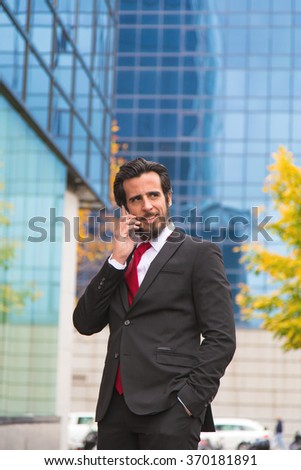 Bearded man dressed with a suit speaking with a smartphone