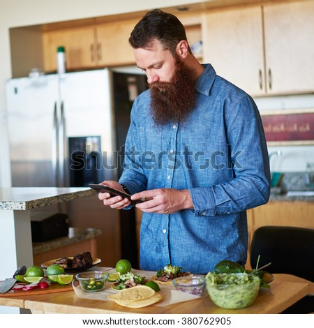bearded man following recipe on tablet to make street tacos shot with selective focus - stock photo