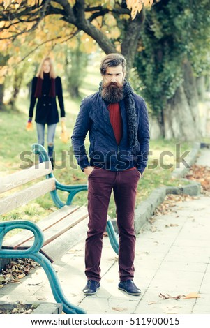 Bearded man hipster with beard and moustache dating with pretty girl near bench outdoors in autumn park on natural background