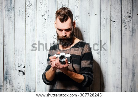 Bearded man holds a vintage film camera. Shot on bright white painted wooden background. - stock photo