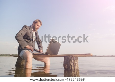 Bearded man in a gray jacket and underwear sitting on a wooden bench in the water with a laptop at sunset or sunrise