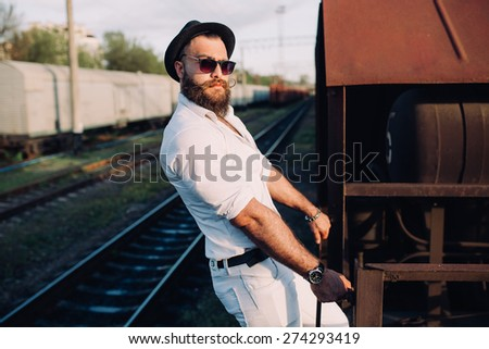 bearded man in a sunglasses posing on the old train