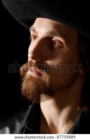 bearded man in hat, low key portrait - stock photo