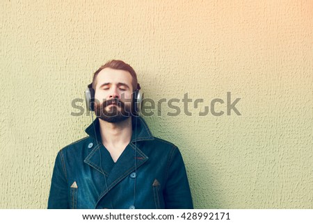bearded man  in headphones listening to music. space for text - stock photo