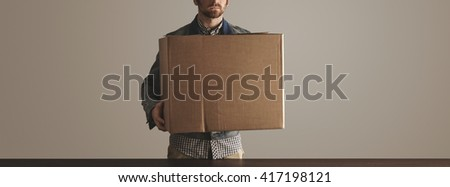 Bearded man in jeans work jacket holds big carton paper box with goods above wooden table. Special delivery, retail shipping, courier mailing post box - stock photo
