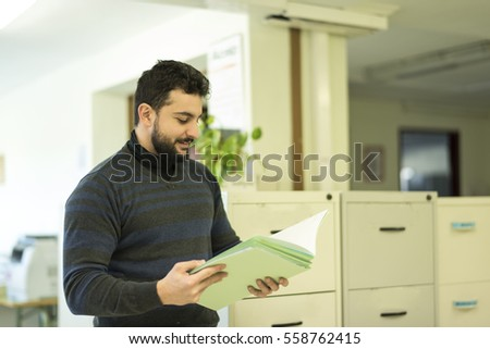 Bearded man in office looking some files
