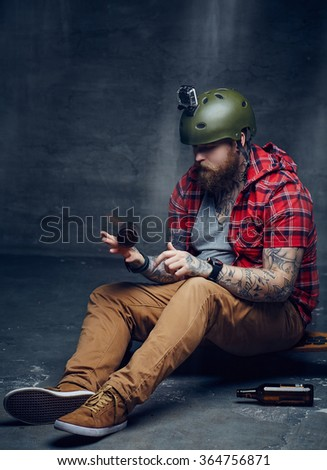 Bearded man in red shirt sitting on long board.