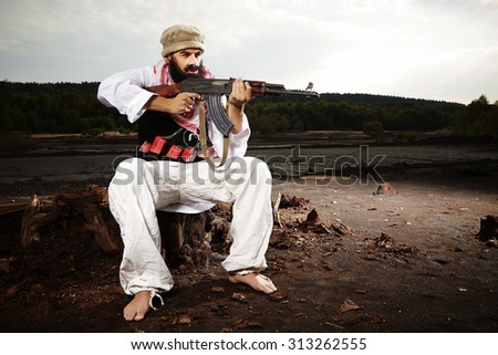 Bearded man in style of suicide bomber - stock photo