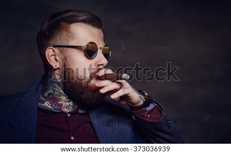 Bearded man in sunglasses and tattooes on his body smoking cigar. - stock photo