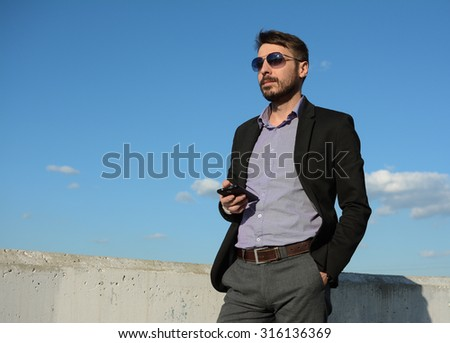 Bearded man in sunglasses with a phone is standing against a background of the sky