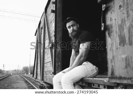 bearded man in the cap posing on the wagon train and travel, black and white